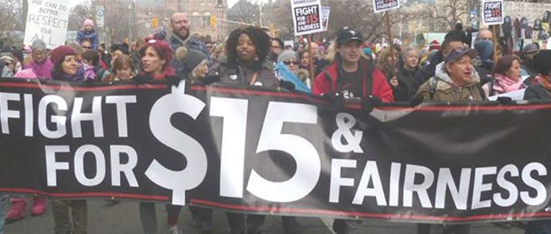 Photo of people marching in the street holding a Fight for $15 & fairness banner
