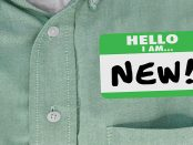 """Photo of a close-up of a shirt pocket with a """"hello my name is new"""" sticker on it."""