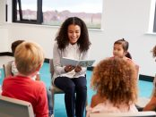 Photo of teacher reading to children in a classroom