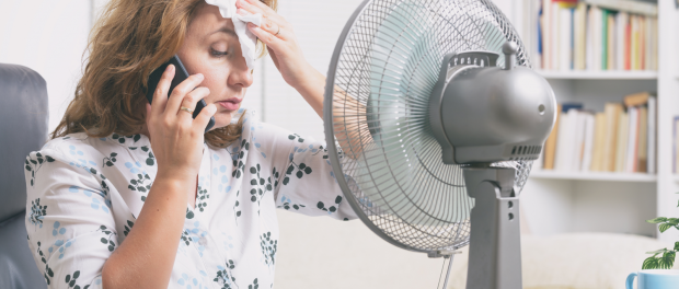woman sitting at her work desk with fan blowing in face