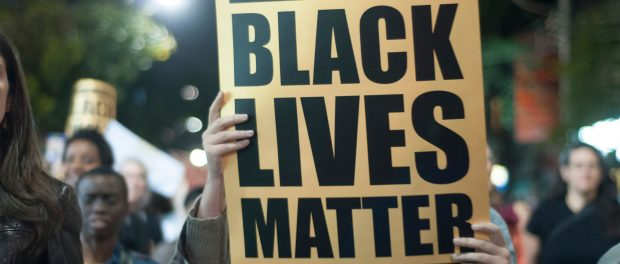 A protester holding up a sign that says Black lives matter