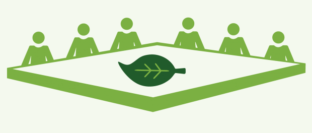 image of people sat around a table with a leaf placed in the middle