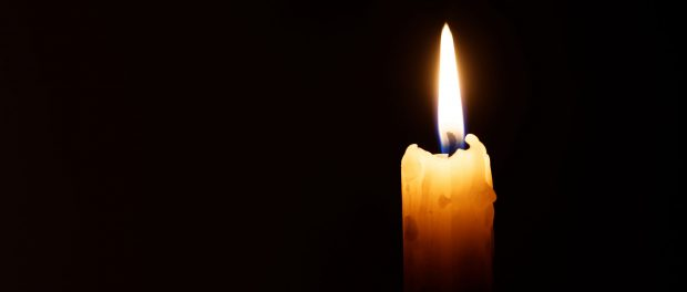 Burning candle isolated against a black background