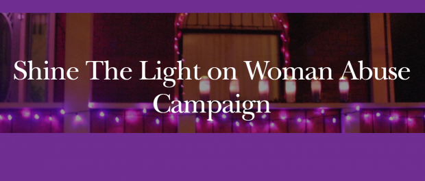 image of a city at night with candles with the words Shine the lights on woman abuse campaign